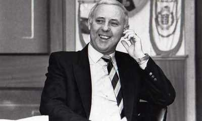 JIM MCLEAN SITS BEHIND HIS DESK AND LAUGHS