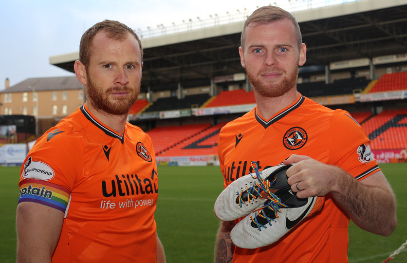 mark reynolds and mark connolly hold up the boots showing our support for rainbow laces